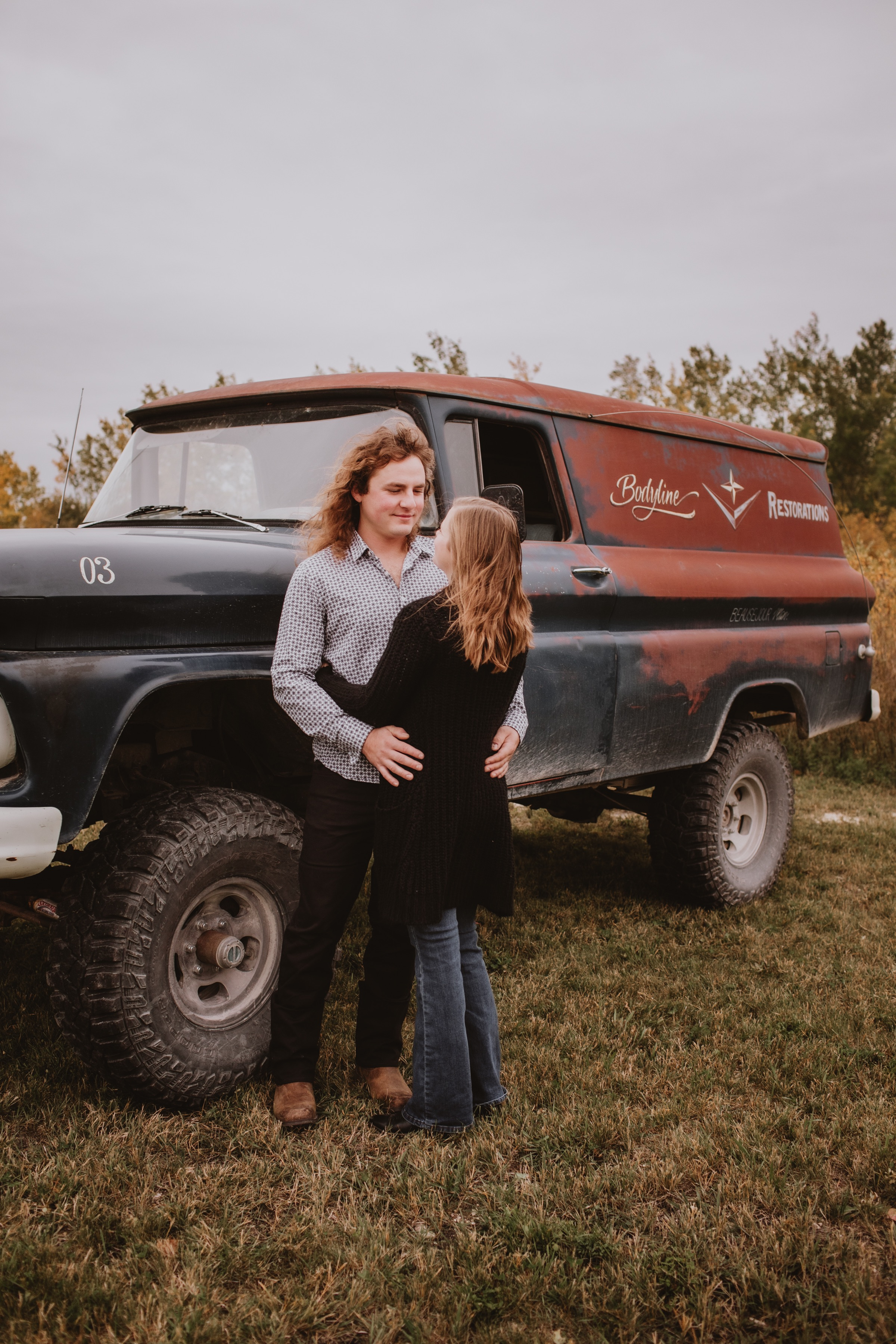 Couple leans on restored Vintage truck - fall engagement photo session.