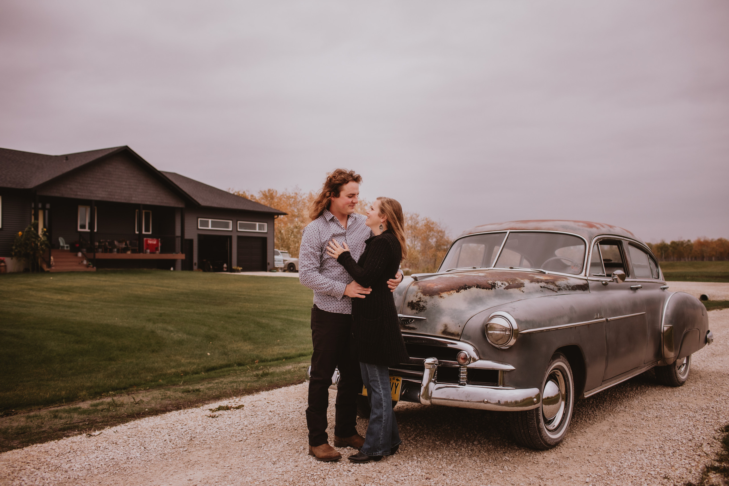 Couple Poses by restored vintage car and home in rural Manitoba, during engagement session.