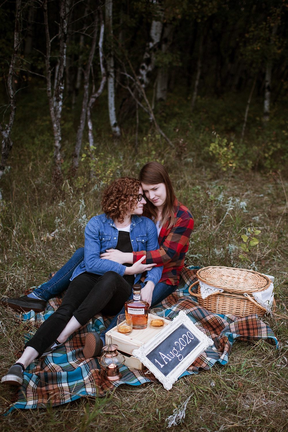 Couple cuddles on picnic blanket during their fall engagement photos.