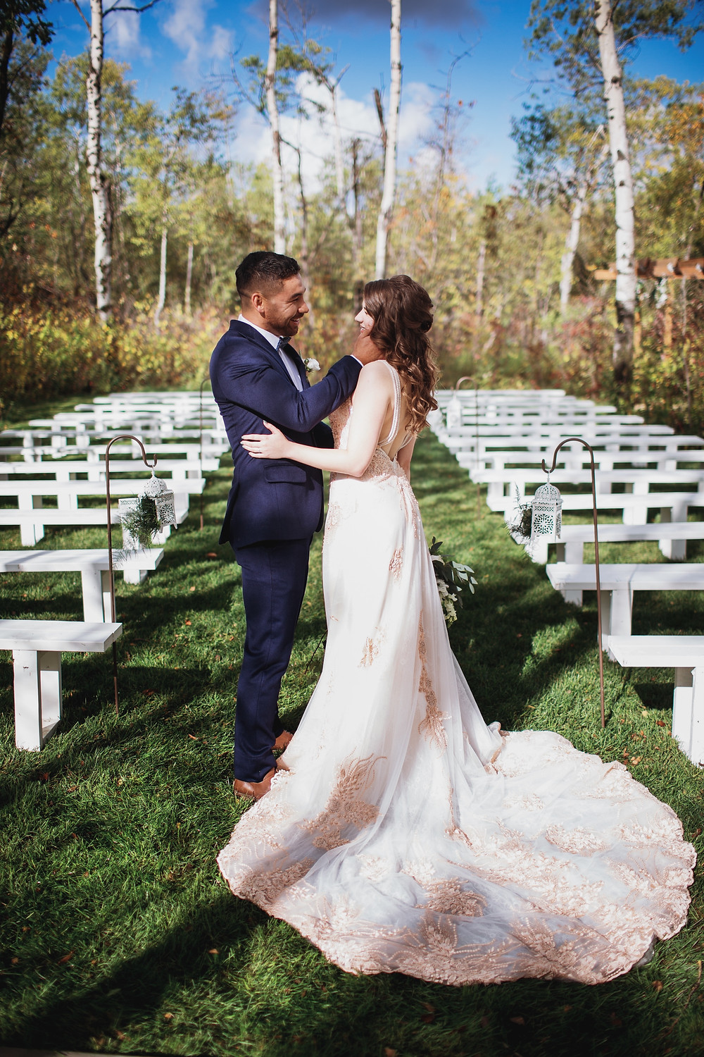 Blush wedding gown with navy groom's suit.