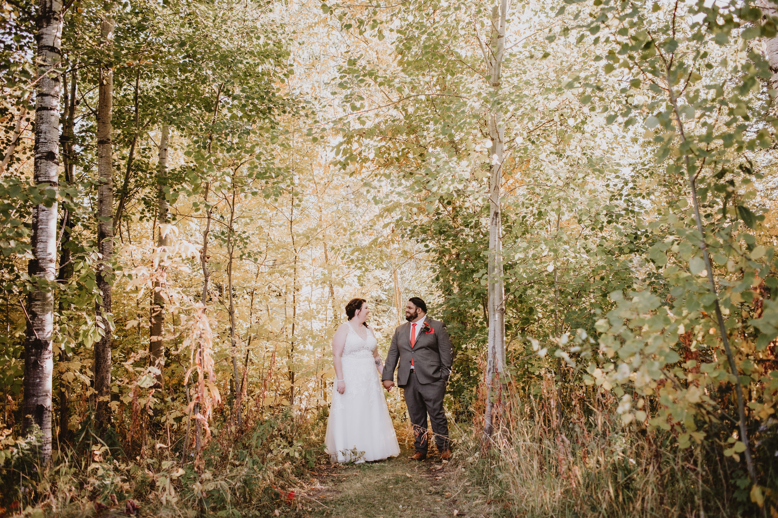 Wedding Couple in Forest, posing for fall wedding day portraits.