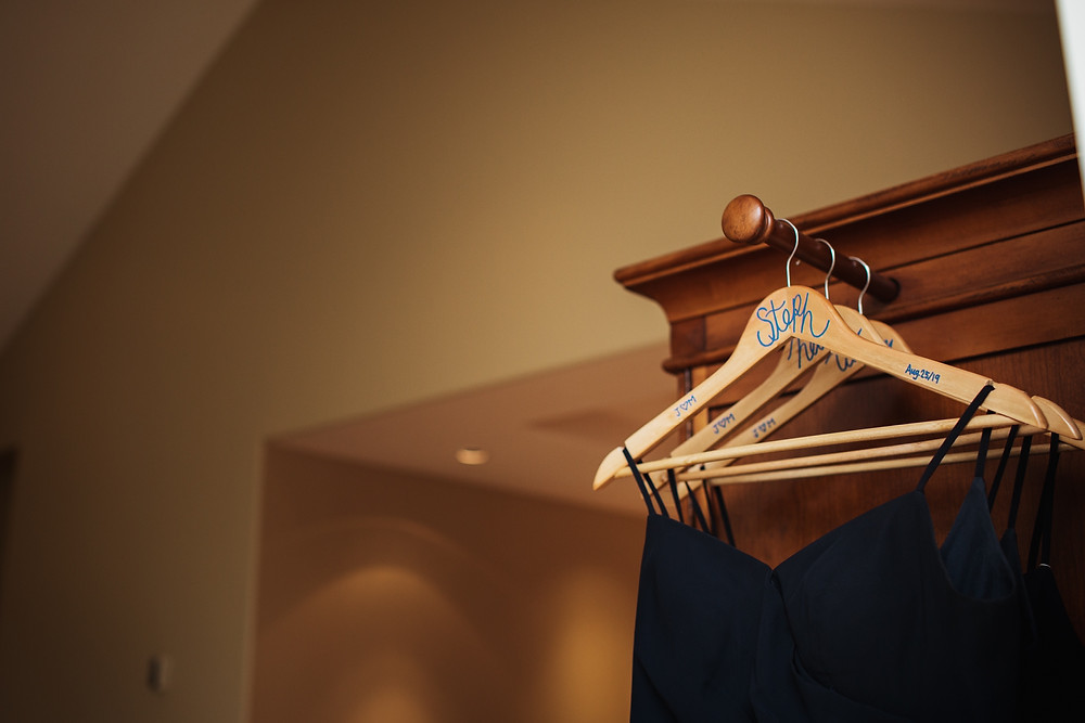 Navy bridesmaid dresses on wooden hangers with bridesmaids names.