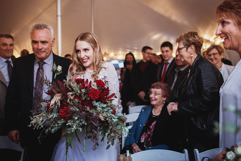 Father-of-the-bride walks bride down the aisle in tent wedding ceremony.