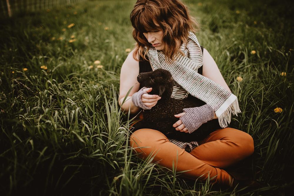Female fibre artist holds lamb for brand photoshoot.