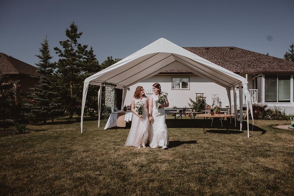 Smiling Winnipeg brides walk to backyard ceremony space.