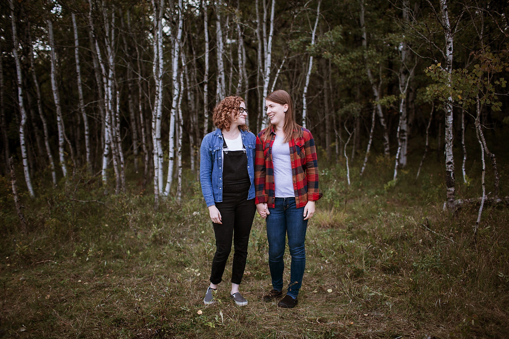 Future brides hold hands in the forest during their engagement photos.