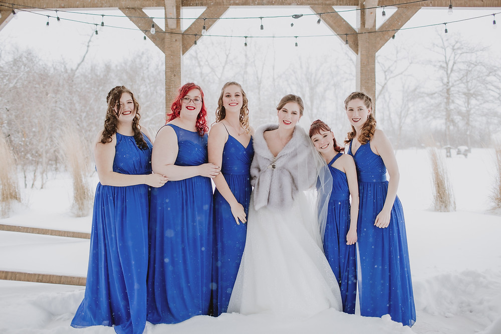 Winter bride with five bridesmaids in blue dresses.