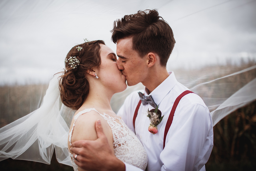 Bride and groom kiss, veil in the wind.