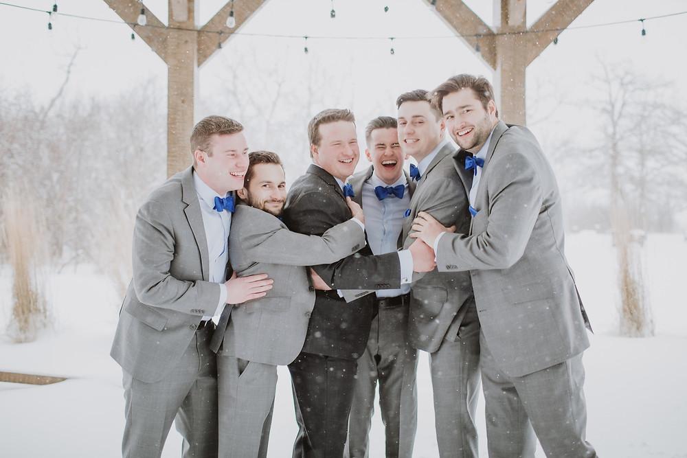 Groomsmen surround groom in group hug.