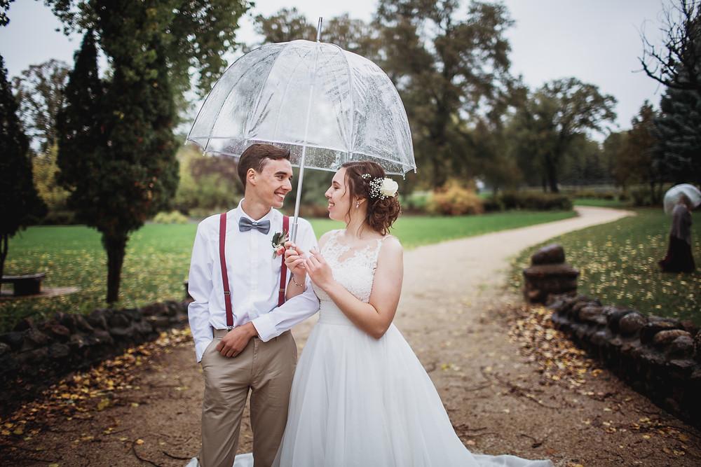 Bride and groom under umbrella.