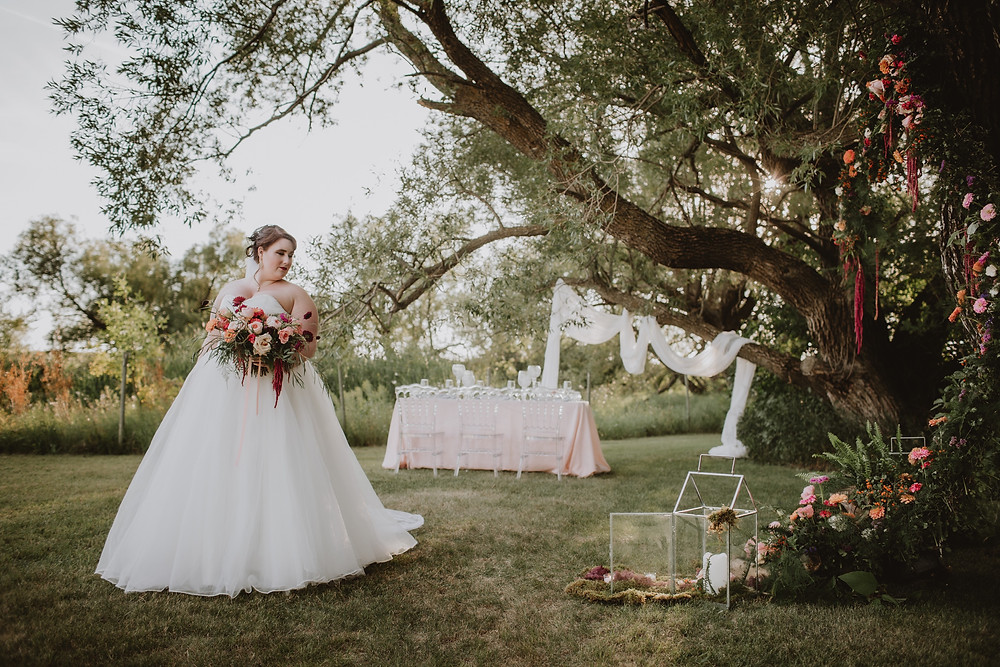 Bride poses with floral arch, tree altar and intimate dinner reception table.