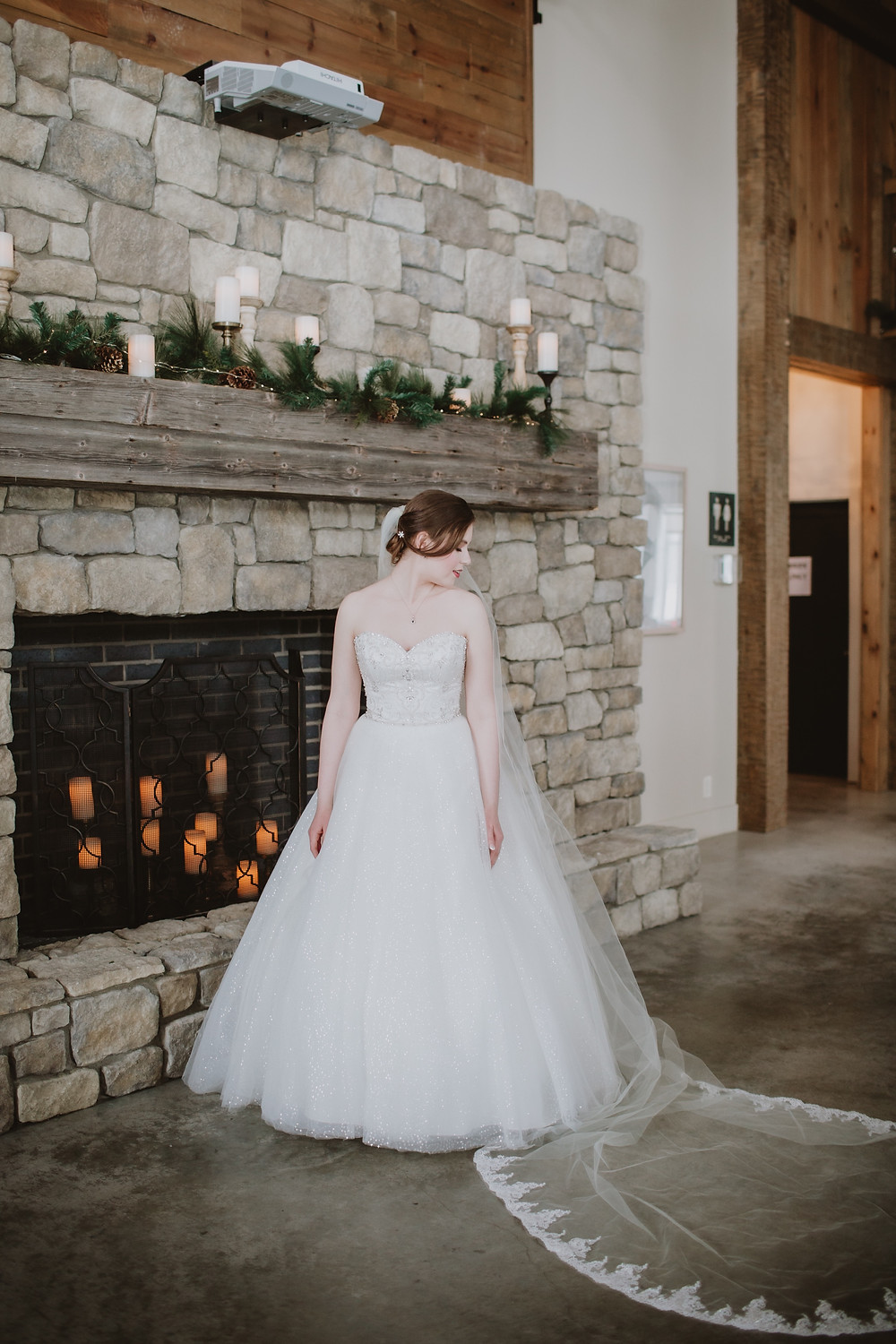 Manitoba bride poses in front of the fireplace at Hawthorne Estates.