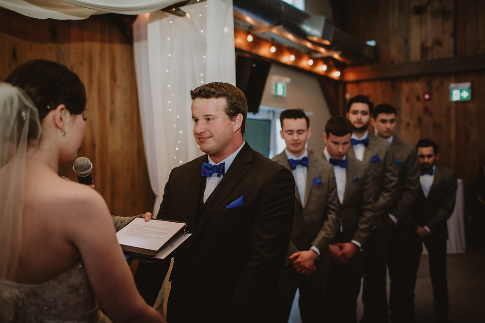 Groom exchanges vows with bride.