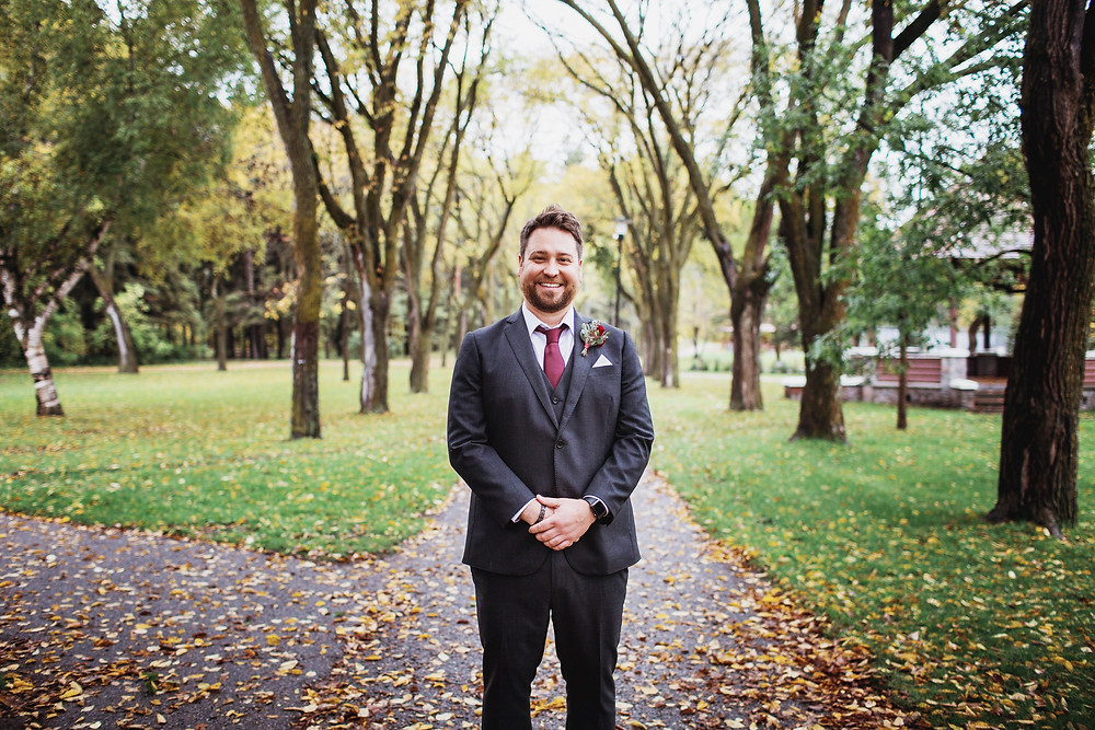 Groom with black suit and maroon tie, fall wedding inspiration.