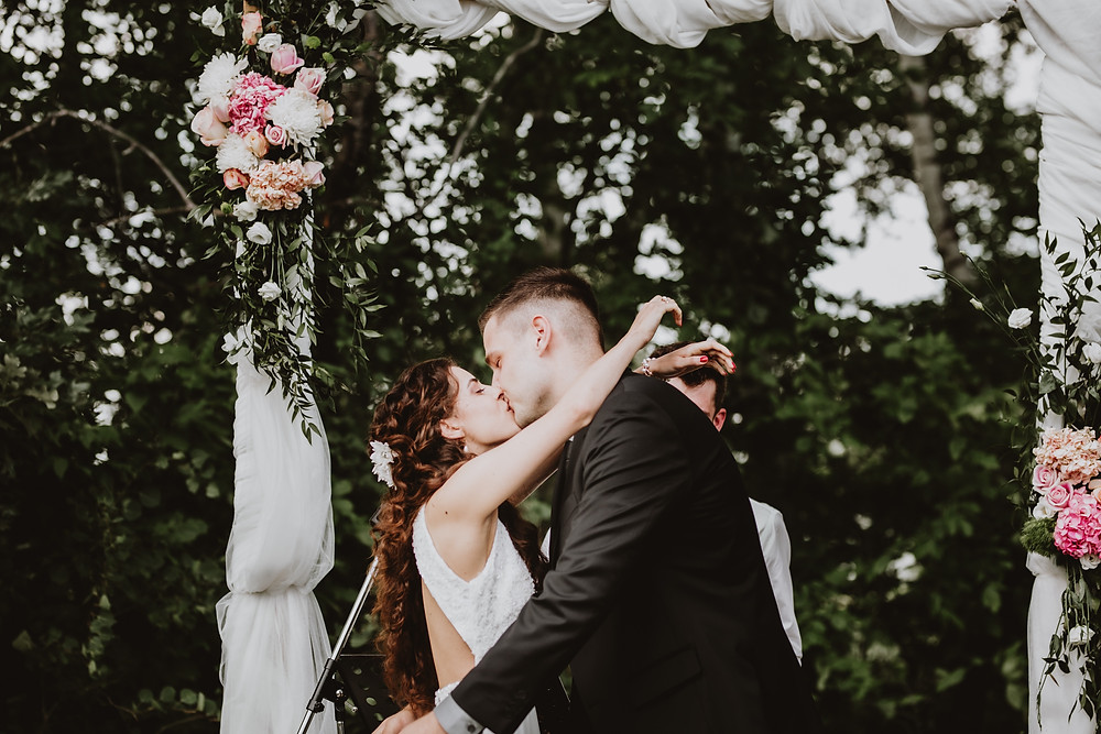 Bride and groom kiss at the altar, backdropped by arch decorated with pink/blush florals.