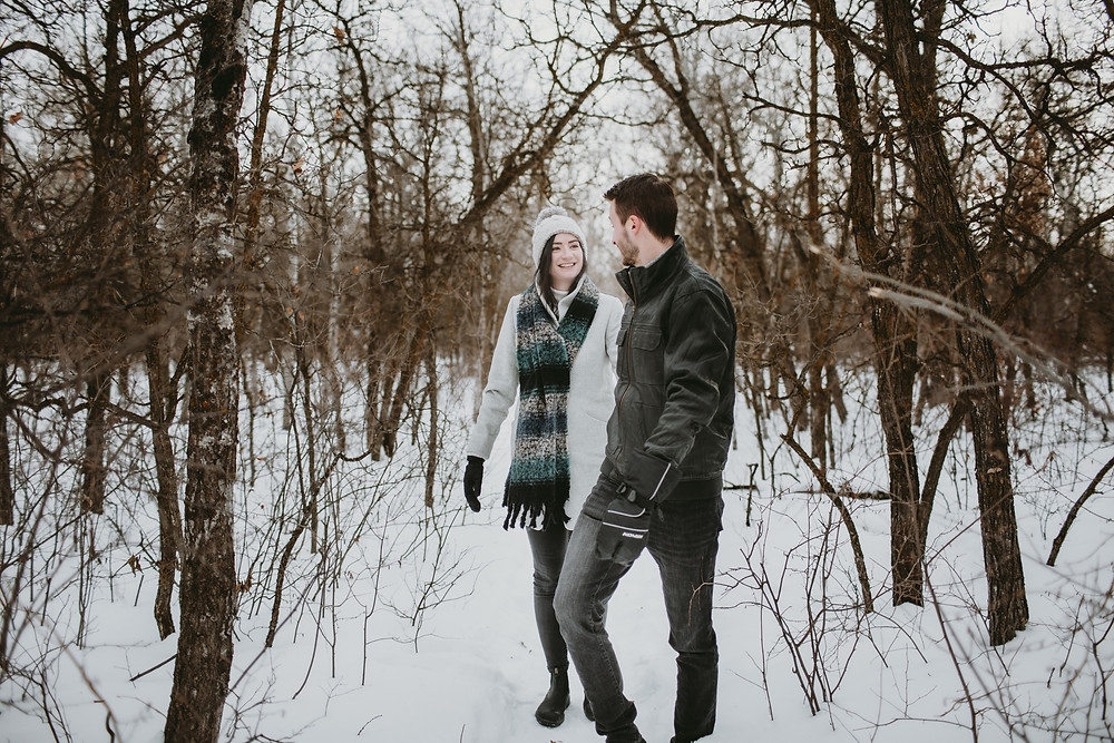 Engaged couples walk through forest.