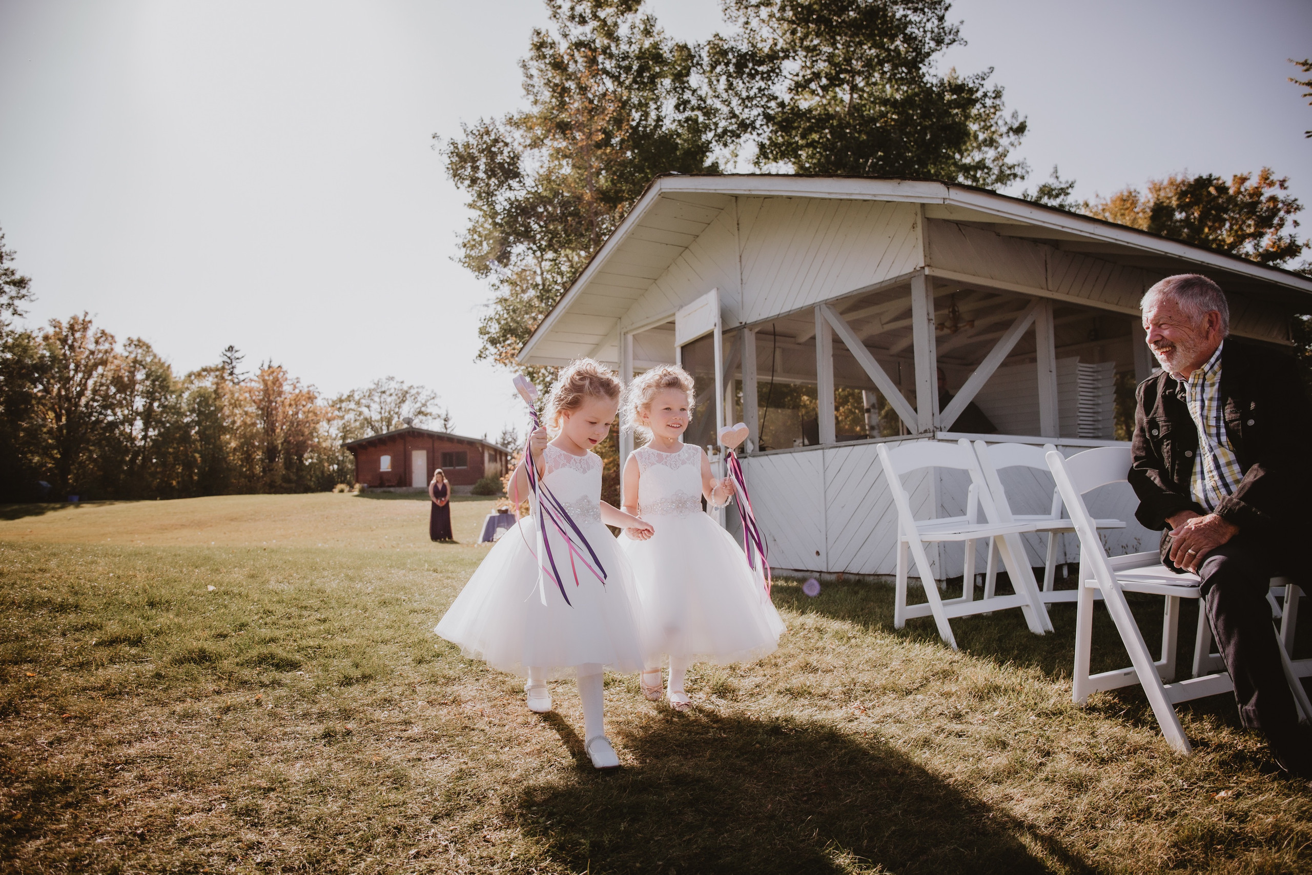 Flower Girls with Heart Wands walk down aisle during fall Manitoba wedding.