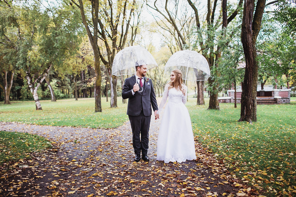 Bride and groom walking down a path under their clear umbrella.