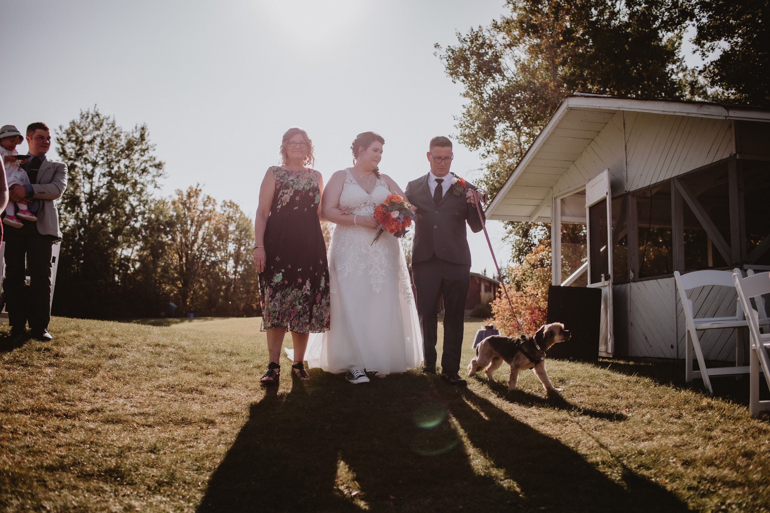 Bride Walks Dog Down Aisle in riverside wedding ceremony at Rivers Edge