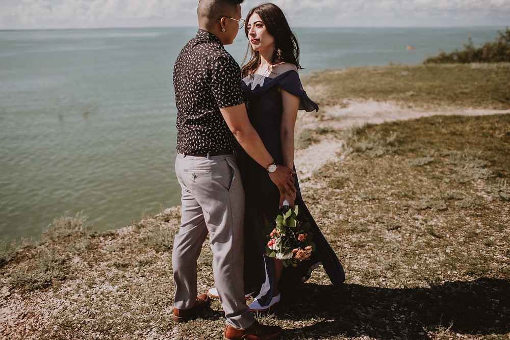 Romantic summer engagement session, on a cliff overlooking water.