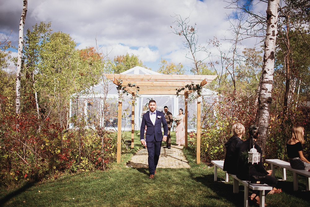 Groom walks down aisle in navy suit by Eph Apparel