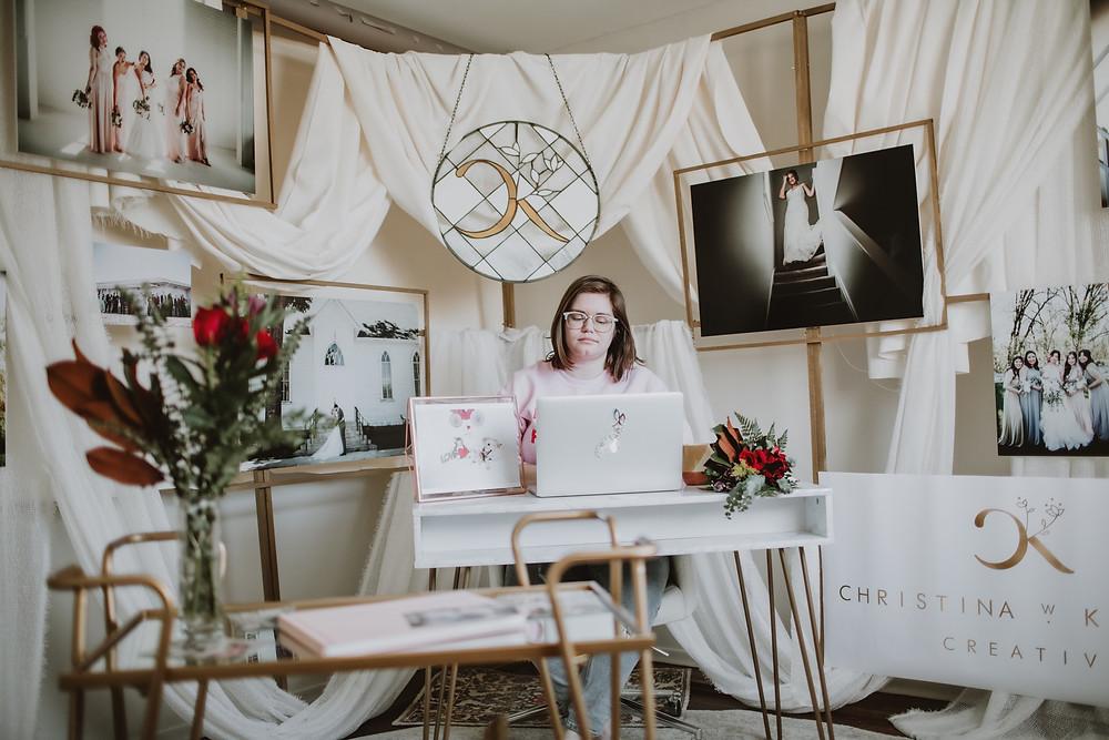 Wedding photographer sits at desk.