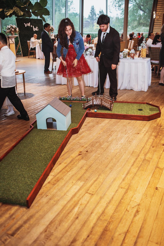 Wedding guests enjoy mini golf in their Winnipeg wedding reception in Assiniboine Park.