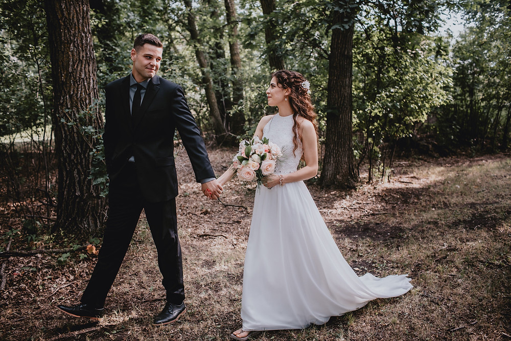 Bride and groom take a walk on through the woods.