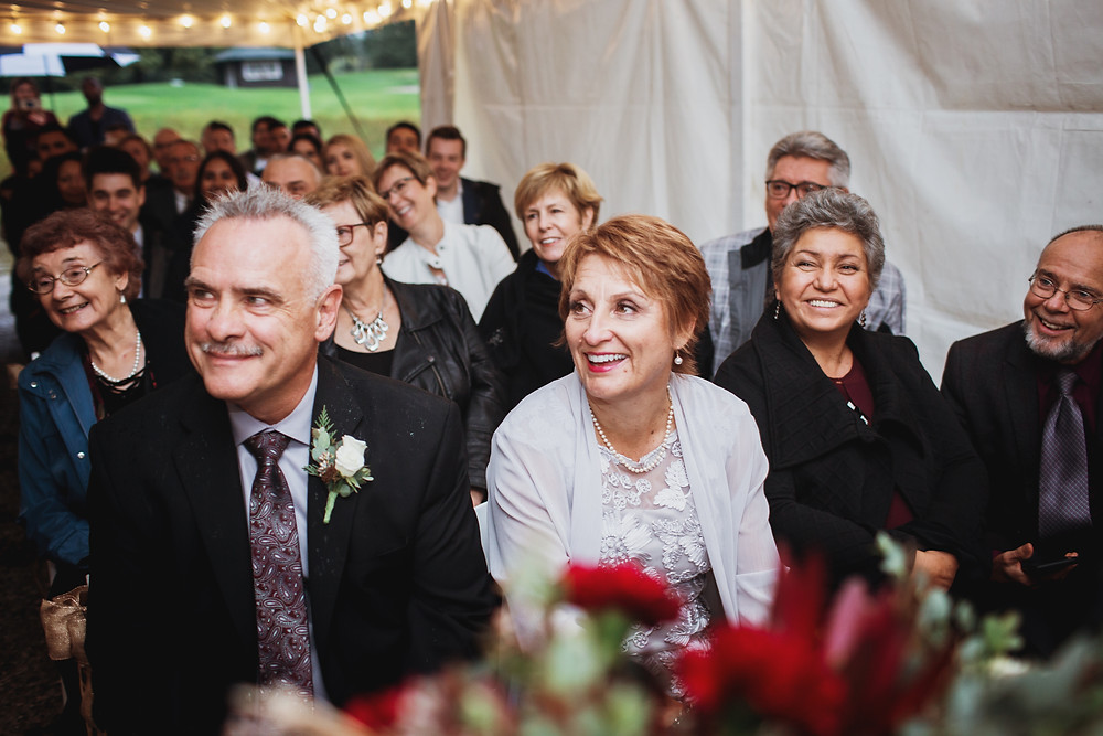 Guests happily watch bride and groom exchange vows in fall wedding.