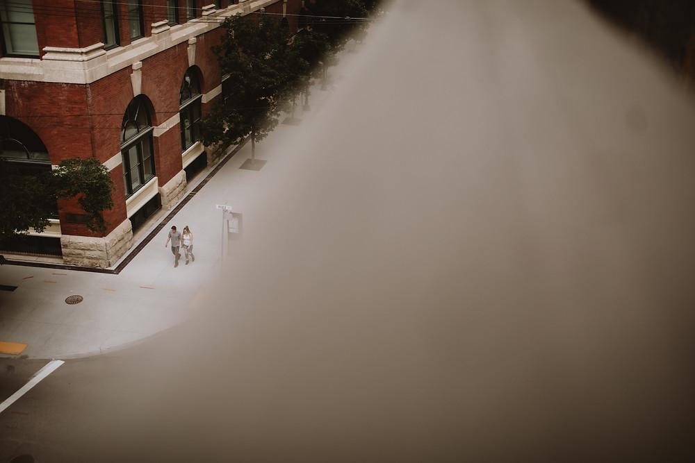 Couple walking in downtown Winnipeg, photo taken from a few floors up.