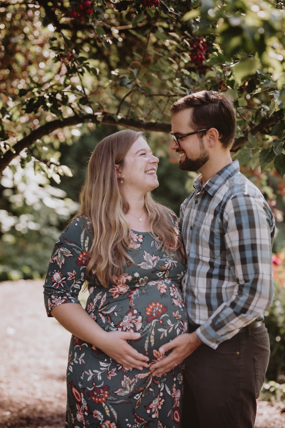 Smiling couple embraces during maternity photoshoot.