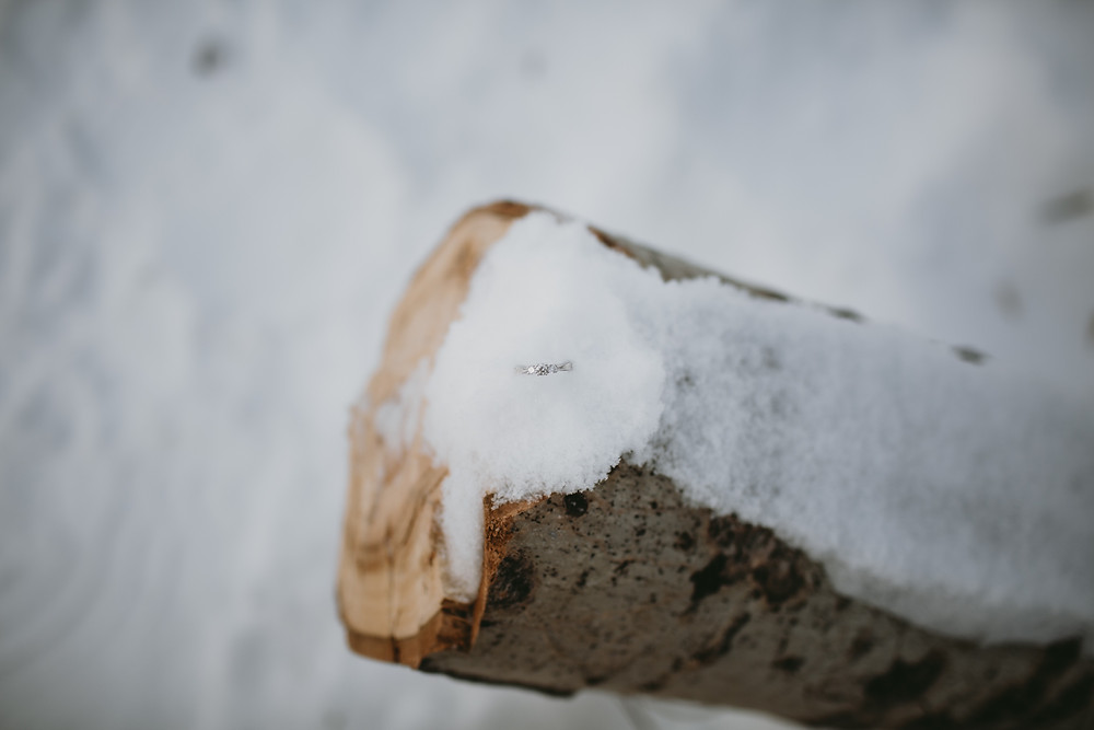 Engagement ring on snowy log.