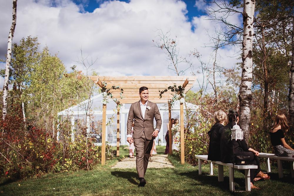groomsman walks down aisle in brown suit by Eph Appareal.