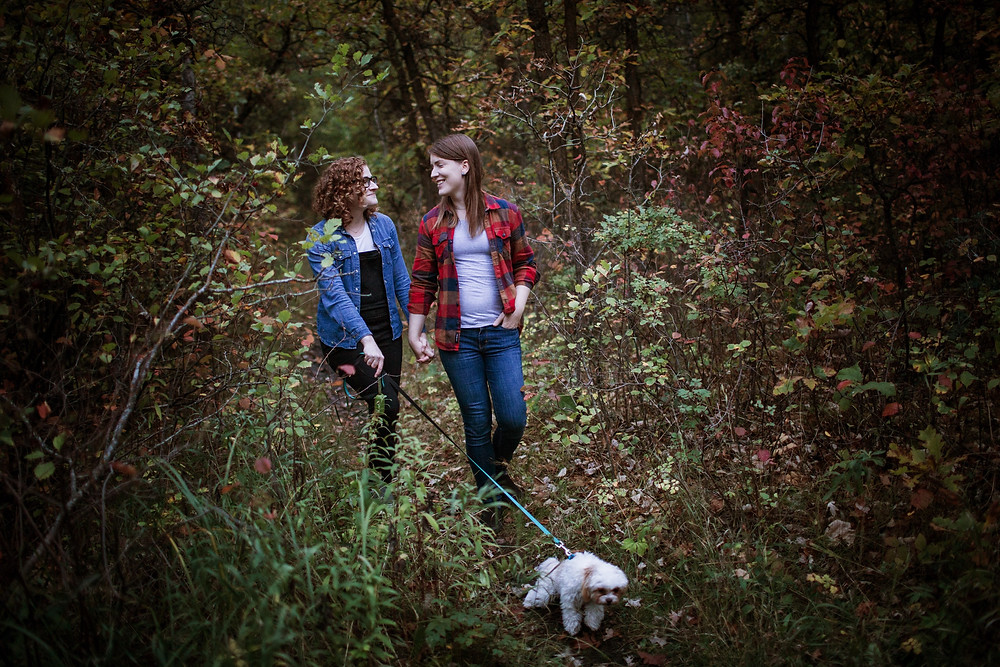 Fall forest engagement photos; same-sex couple walks pup through the forest.