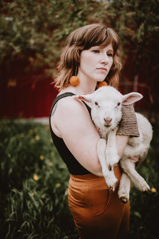 Female fibre artist holds lamb during brand shoot.