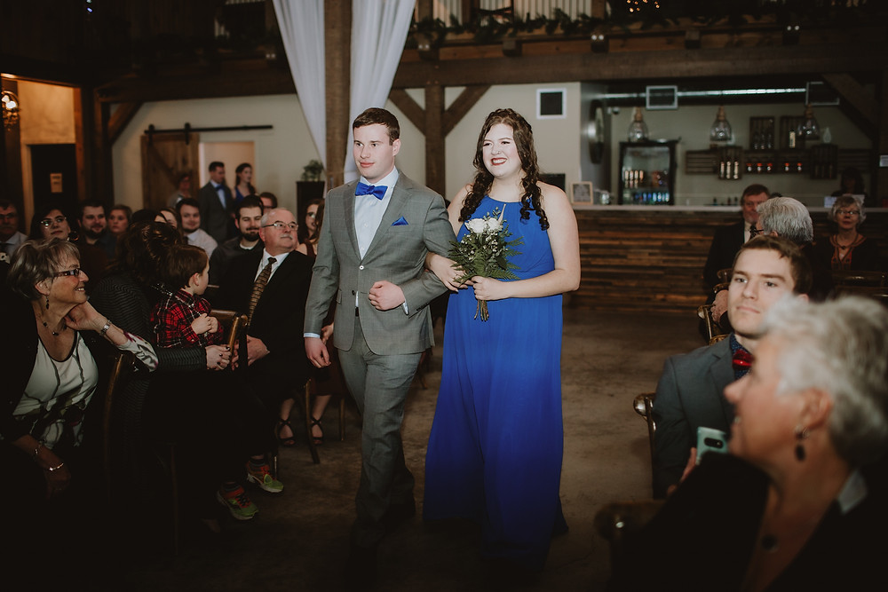 Bridesmaid and groomsman walk down aisle at Hawthorne Estates winter weddings.