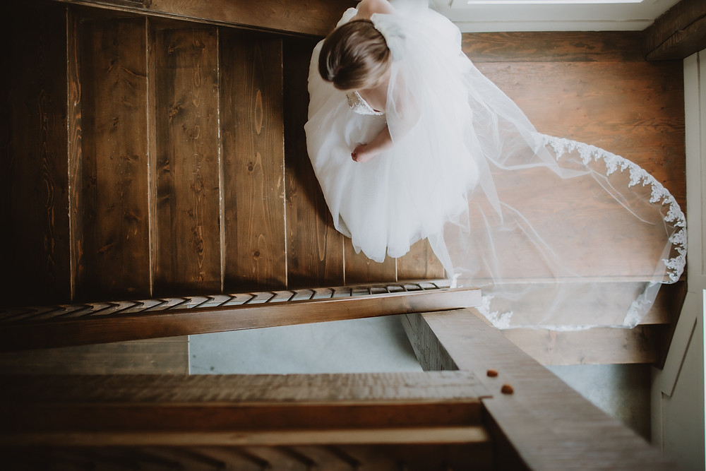 Bride walks upstairs, showcasing her handmade cathedral veils.