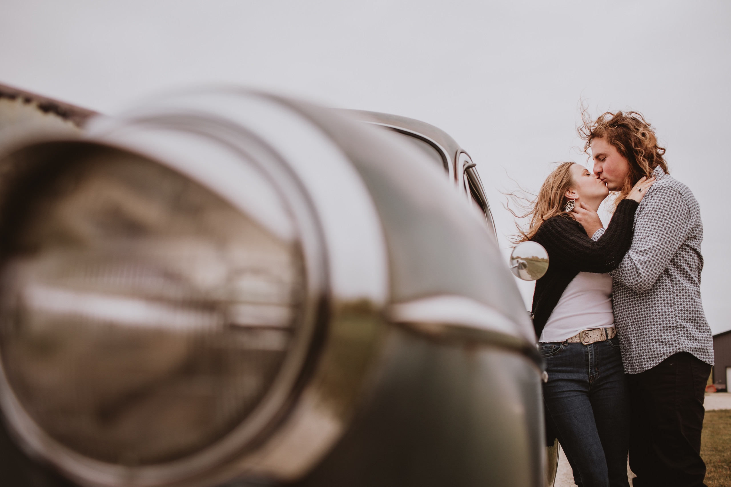 Couple Kisses by Vintage Car during fall engagement photoshoot in rural Manitoba.