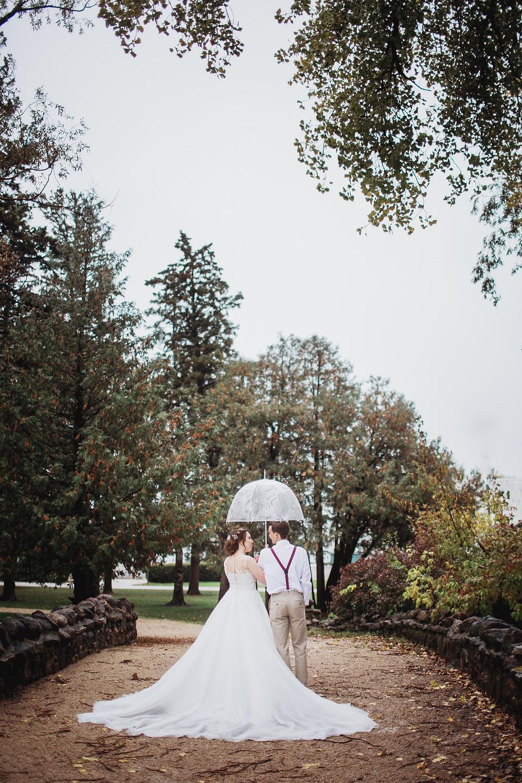 Bride and groom walk under umbrella on their rainy fall wedding day.