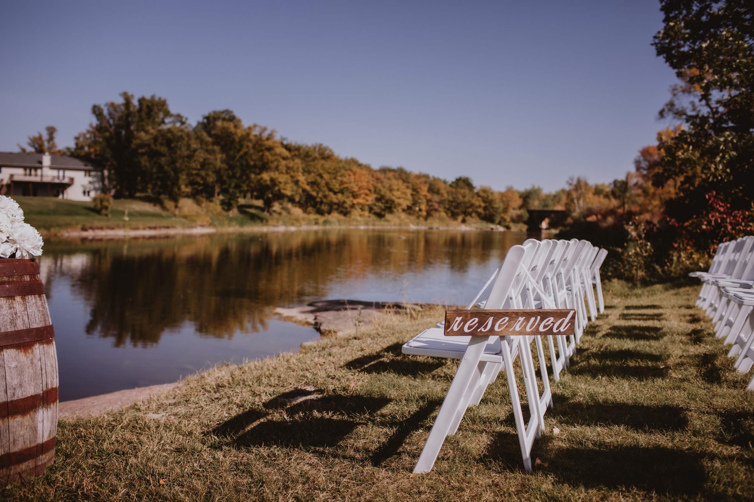 Riverside Wedding Ceremony with reserved sign for guest seating.