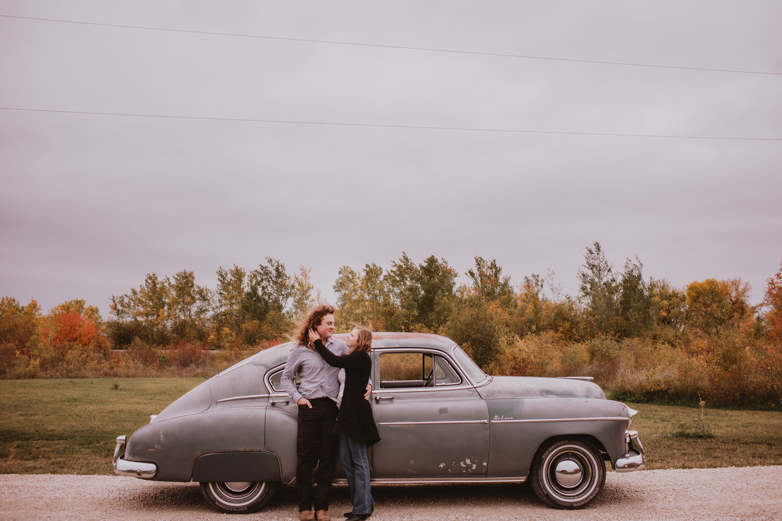 A Couple and their vintage car during fall engagement photoshoot