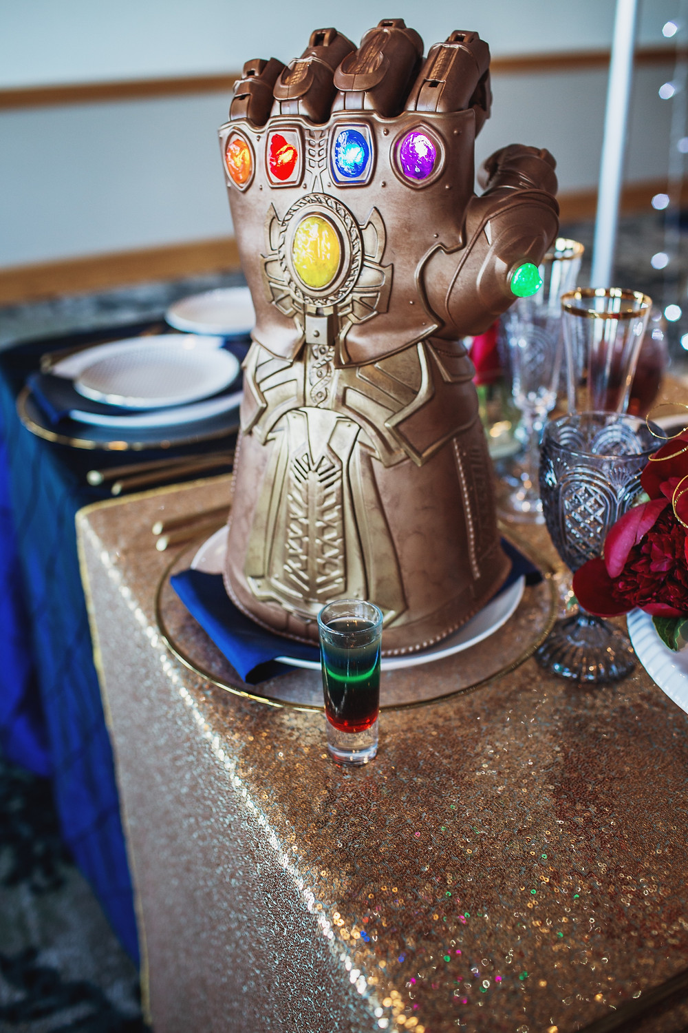 "Marvel's infinity gauntlet pictured with the ""infinity shot"" an Avengers-themed cocktail inspired by the infinity stones."