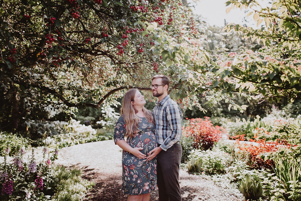 Couple poses for photos under fruit tree in English Gardens.