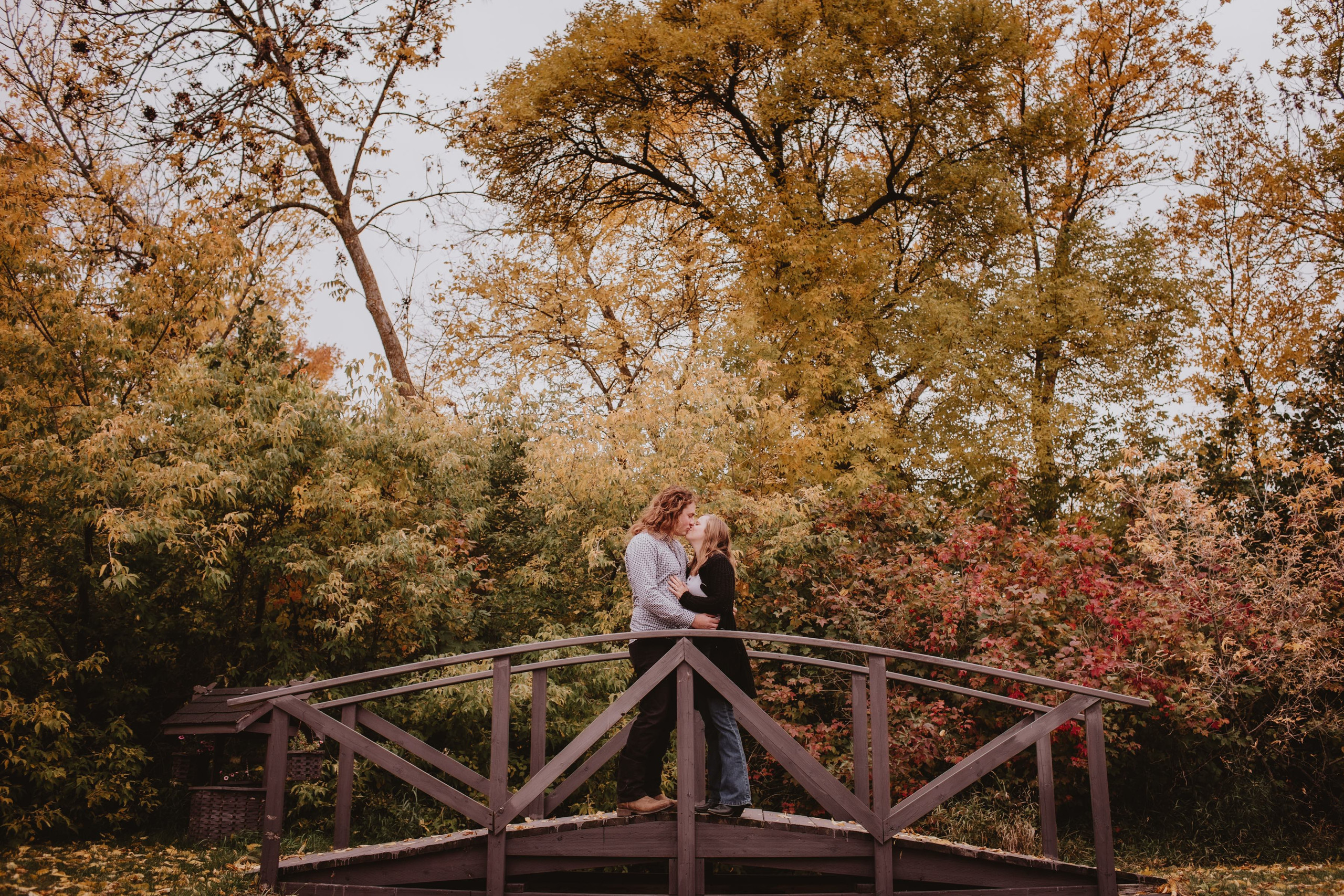 Couple Kisses on Bridge during fall engagement pictures.