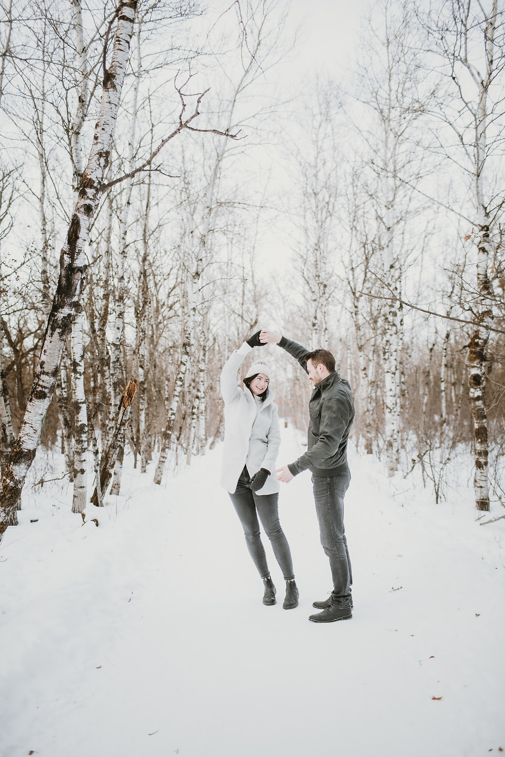 Couple dances in snowy forest.