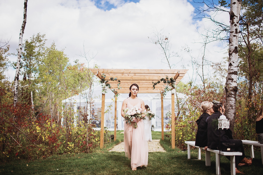 Bridesmaid walks down aisle in s down aisle in light pink gown from Pearl and Birch