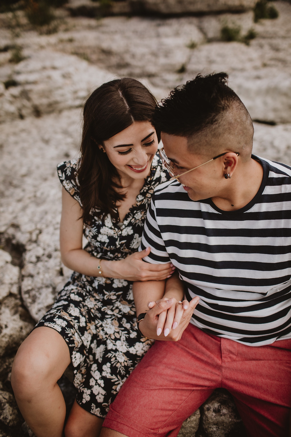 Smiling couple sits on rocks during engagement session.
