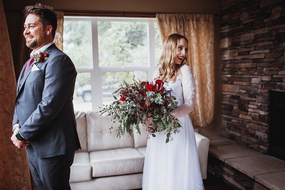 First look between wedding couple, bride and groom see each other for the first time in their rented cabin in Clear Lake, Manitoba.