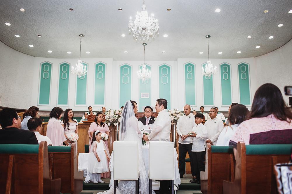 Wedding ceremony in Winnipeg church, bride and groom share their wedding vows.