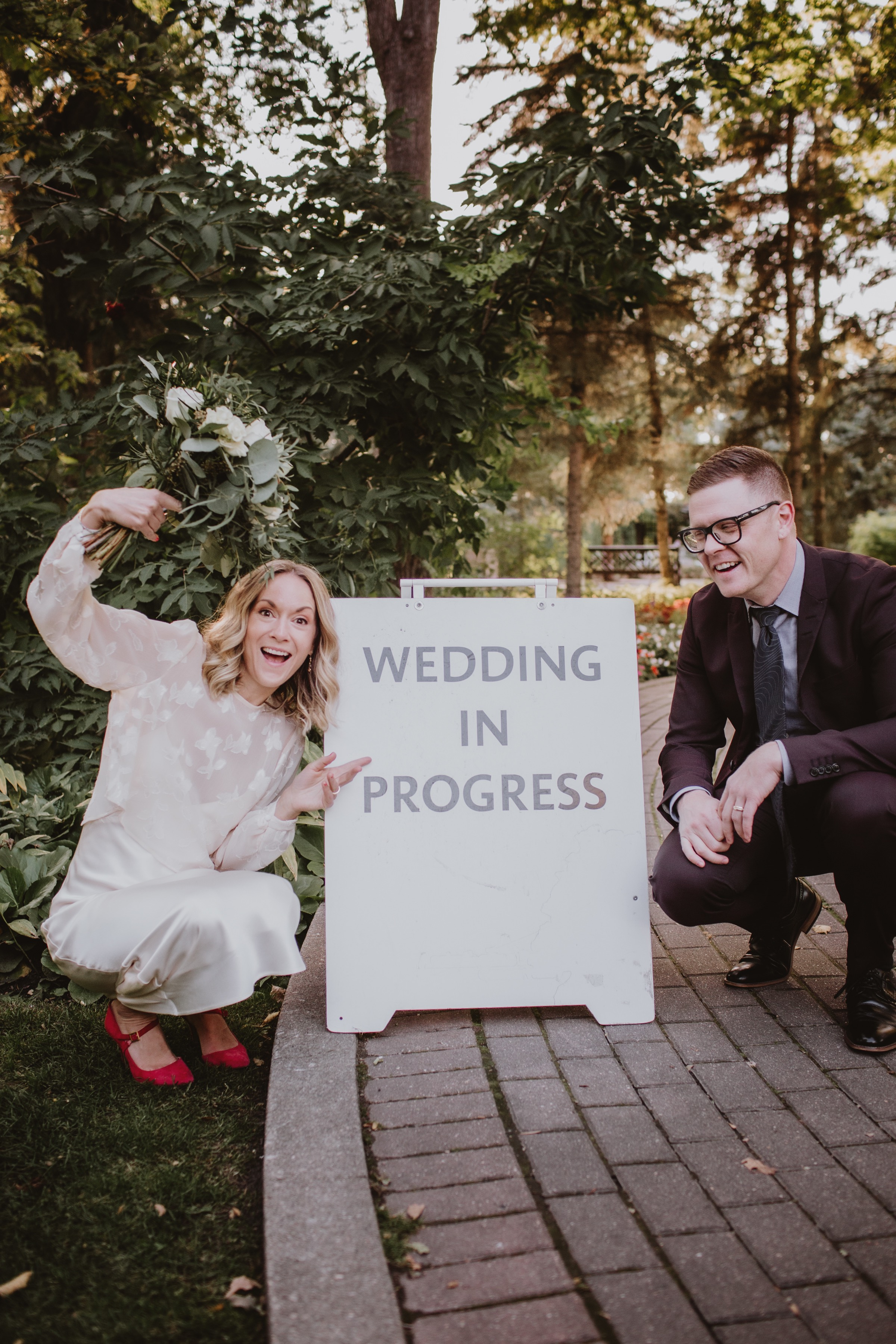 "Excited Bride and Groom pose by ""wedding in progress"" sign."